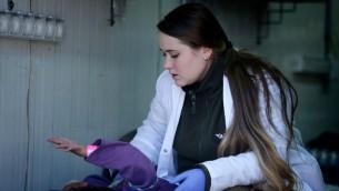 عاملة خدمات طبية في المستشفى العسكري في هظبة الجولان تعالج طفل سوري فبراير 2014 (كوبي جدعون/ جي بي أو/ فلاش 90)
