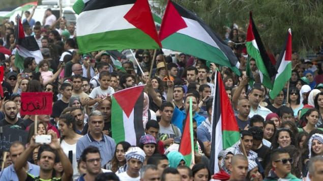 عرب إسرائيلون يصمدون العلم الفلسطيني وهم يسيرون من اجل  حق العودة للاجئين الفلسطينيين الذين فروا من ديارهم أو طردوا أثناء حرب 1948 التي أعقبت قيام دولة إسرائيل، بالقرب من طبرية في شمال إسرائيل، يوم 6 مايو، عام 2014. AFP PHOTO / أحمد غرابلي