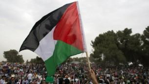 العلم الفلسطيني خلال مسيرة من اجل  حق العودة للاجئين الفلسطينيين الذين فروا من ديارهم أو طردوا أثناء حرب 1948 التي أعقبت قيام دولة إسرائيل، بالقرب من طبرية في شمال إسرائيل، يوم 6 مايو، عام 2014. AFP PHOTO / أحمد غرابلي