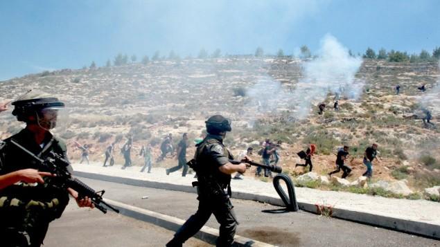 شرطة الحدود الإسرائيلية ترمي قنابل الغاز المسيل للدموع  خلال اشتباكات مع المتظاهرين الفلسطينيين بمناسبة الذكرى 66 للنكبة الخميس مايو 15، 2014، بالقرب من قرية الولجة بالضفة الغربية، جنوب القدس ( AFP / موسى الشاعر)