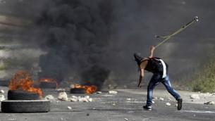 متظاهر فلسطيني ملثم يستخدم مقلاع لالقاء حجر على قوات الأمن الإسرائيلية خارج سجن عوفر في الضفة الغربية قرية بيتونيا،  16 مايو 2014 ( AFP / عباس المومني).