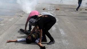 """اشتباكات مع أفراد من قوات الأمن الإسرائيلية خارج سجن عوفر في قرية بيتونيا في الضفة الغربية، في 16 مايو عام 2014، بعد مقتل شابين فلسطينيين برصاص شرطة الحدود الإسرائيلية خارج السجن خلال اشتباكات عقب مظاهرة بمناسبة """"النكبة"""" (AFP PHOTO / ABBAS MOMANI)"""