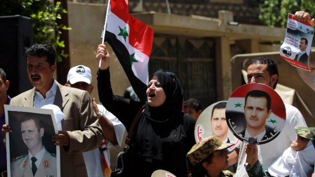صورا للرئيس السوري بشار الاسد خلال تظاهرة لدعم إعادة انتخابه في 24 مايو 2014 خارج السفارة السورية في العاصمة اليمنية صنعاء.  AFP PHOTO / MOHAMMED HUWAIS