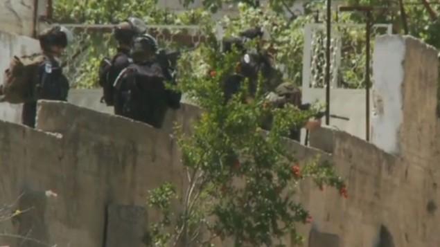 جندي إسرائيلي مشيرا بندقيته على مجموعة من الفلسطينيين أثناء مظاهرة يوم النكبة في بلدة بالضفة الغربية بيتونية  15 مايو. (صورة شاشة سي ان ان)