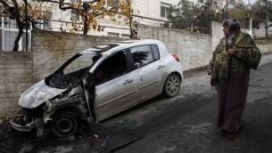 فلسطينية تقف امام سيارة حرقها المستوطنون في مخيم الجلبون شمال رام الله ٢٠١٣ (عصام ريماوي/ فلاش ٩٠)