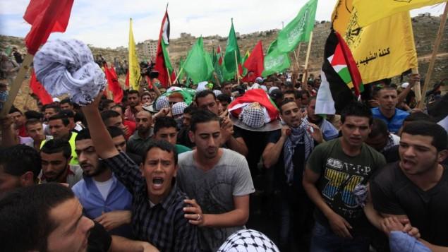 فلسطينيون اثناء الحداد على مقتل اثنين من المراهقين الفلسطينيين، برصاص الجيش الإسرائيلي، في جنازة مشتركة في بلدة بيرزيت بالضفة الغربية، شمالي مدينة رام الله، على 16 مايو 2014 ( Issam Rimawi/Flash90)