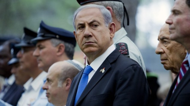 رئيس الوزراء بنيامين نتنياهو خلال مراسيم احياء ذكرى ضحايا الحروبات الاسرائيلة 5 مايو 2014 الى يمينه شمعون بيريس ( AFP/POOL/JIM HOLLANDER)