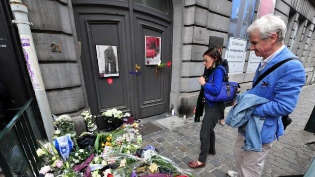 رجل يهودي  أمام الزهور ونصب تذكاري مؤقت في مدخل المتحف اليهودي في بروكسل  25 مايو عام 2014.  AFP PHOTO / BELGA / THIERRY ROGE