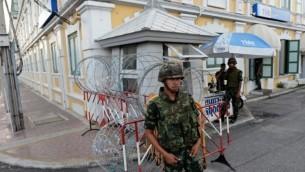الجنود التايلانديين عند حاجز طريق خارج مبنى وزارة الدفاع (الخلفية) بعد أن أعلن قائد الجيش التايلاندي ان القوات المسلحة والاستيلاء على السلطة، في بانكوك يوم 22 مايو 2014  AFP/Christophe Archambault