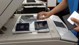 موظف وكالة الأمم المتحدة للاجئين  بفحص جوازات سفر للاجئين السوريين في مركز تسجيل اللاجئين، في ميناء مدينة طرابلس الشمالية  29 مايو 2014 و 31     AFP PHOTO/ANWAR AMRO
