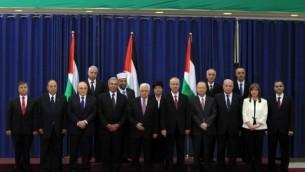 رئيس السلطة الفلسطينية محمود عباس محاط بوزراء حكومة التوافق بعد اداء اليمين ٢ يونيو ٢٠١٤ (AFP/ABBAS MOMANI)