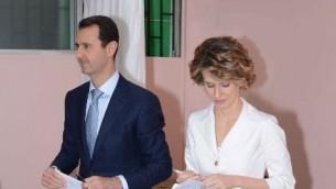 """صورة للنشر صادرة عن صفحة الفيسبوك الرسمية للرئاسة السورية تظهر الرئيس السوري بشار الأسد (C) وزوجته أسماء الأسد (R ) يدلون بأصواتهم في مركز اقتراع في المالكي،  3 يونيو 2014،""""AFP PHOTO / HO /THE OFFICIAL FACEBOOK PAGE OF THE SYRIAN PRESIDENCY"""""""