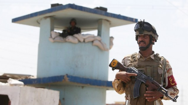 جندي عراقي يقف حارسا عند نقطة تفتيش في بلدة التاجي العراقية، عند مدخل بغداد يوم 13 يونيو 2014 ( Ahmad al-Rubaye/AFP)