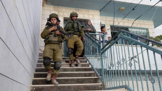 الجنود الإسرائيليون يتركون بيت فلسطيني بعد تفتيش  قرب الخليل في 15 يونيو 2014، أثناء بحثهم عن ثلاثة مراهقين الذين فقدوا بالقرب من مستوطنة بالضفة الغربية.  AFP PHOTO / حازم بدر