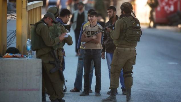 جندي إسرائيلي يتفحص هوية شاب فلسطيني عند نقطة تفتيش في بلدة الخليل بالضفة الغربية،  15 يونيو 2014، AFP PHOTO / مناحيم كاهانا