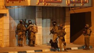 جنود اسرائيليين في محاولة لفتح ابواب متجر مغلقة خلال عملية في أحد شوارع بلدة الخليل بالضفة الغربية  17 يونيو 2014 . AFP PHOTO / حازم بدر