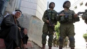 رجل فلسطيني يجلس بجانب الطريق بينما يقف جنديان اسرائيليان في القرية الفلسطينية تفوح غربي الخليل 18, 2014 AFP/HAZEM BADER