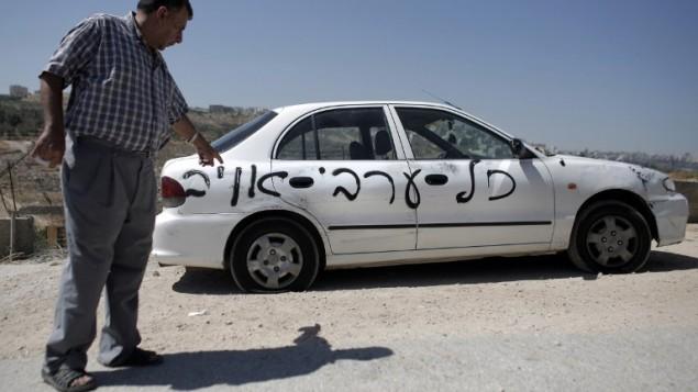"""رجل فلسطيني يشير الى واحدة من عشر سيارات التي تم رشها مع الشعارات العنصرية التي تقرأ في العبرية """"كل العرب أعداء"""" في حي القدس شرق بيت حنينا 23 يونيو 2014  AFP PHOTO / AHMAD GHARABLI"""