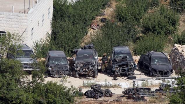 جندي إسرائيلي يتفقد السيارات التي تضررت خلال عملية تفتيش في قرية حلحول، بالقرب من بلدة الخليل بالضفة الغربية، في 29 يونيو عام 2014، AFP PHOTO / حازم بدر