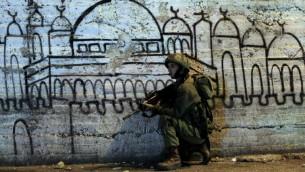 جندي من قوات الأمن الإسرائيلية، اثناء عملية في البحث عن المفقودين،  22 يونيو 2014 في مدينة رام الله بالضفة الغربية  AFP PHOTO / ABBAS MOMANI