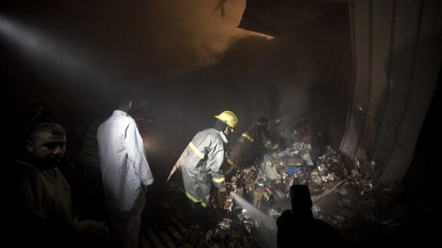 مدنيون ورجال اطفاء فلسطينين يتفحصون الخراب بعد غارة اسرائيلية على غزة June 20, 2014. ( Mahmud Hams/AFP)