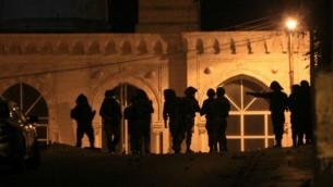 جنود اسرائيليون يقومون بدوريات في الشوارع القريبة من المسجد خلال عملية في مدينة رام الله بالضفة الغربية  17 يونيو 2014  (الصورة الائتمان: AFP / عباس موما)