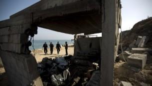 أفراد الأمن الفلسطينية يقومون بتفتش منزل هدم جراء الغارات الجوية الإسرائيلية خلال الليل في وسط قطاع غزة  28 يونيو 2014 ( AFP PHOTO / MAHMUD HAMS).