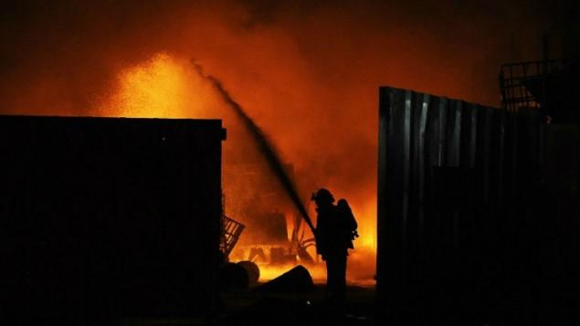 رجال الاطفاء الاسرائيلية يخمدون النار في  مصنع حرق نتيجة ضربة بواسطة صاروخ اطلق من قطاع غزة  28 يونيو 2014 في المنطقة الصناعية في مدينة سديروت الجنوبية AFP/David Buimovitch