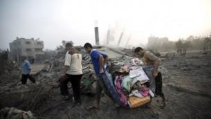 فلسطينيون يحملون اغراضهم بعد غارة اسرائيلية ٨ يوليو ٢٠١٤  AFP/MAHMUD HAMS
