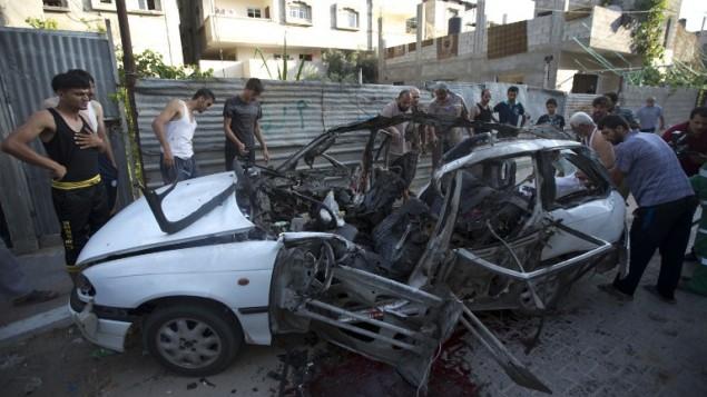 فلسطينيون يتفحصون حطام سيارة ضربتها غارة اسرائيلية مما اسفر عن مقتل ٣ عناصر للجهاد الاسلامي ١٠ يوليو ٢٠١٤ (آ ف ب/ محمود حمص)
