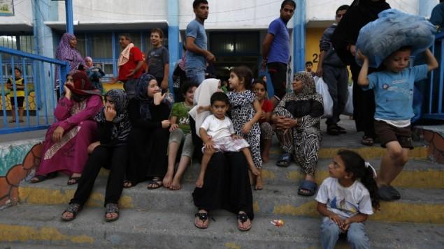 الفلسطينيون يجدون مأوى في مدرسة للأمم المتحدة بعد اخلاء منازلهم بالقرب من الحدود في مدينة غزة يوم 13 يوليو 2014 AFP PHOTO / MOHAMMED ABED