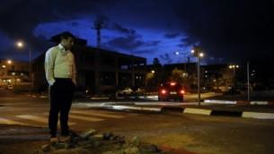 اسرائيلي يقف بجانب حفرة الناجمة عن صاروخ أطلق من قطاع غزة، في مدينة سديروت الاسرائيلية في النقب الغربي الأربعاء 12 مارس، 2014 AFP/David Buimovitch