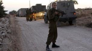 توضيحية: جندي اسرائيلي يحرس مدخل قرية حلحول بعد حظر التجول  30 يونيو 2014 (AFP PHOTO/ HAZEM BADER)