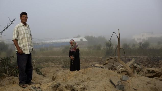 رجل وامرأة فلسطينيين يتفحصان موقع اصابة الغارة الجوية الاسرائيلية على خان يونس ٨ يوليو ٢٠١٤ (عبد محمد/ أ ف ب)