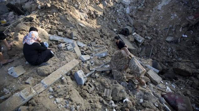 فلسطيني يحمل قطعة اثاث من بين حطام بيت اصيب بالغارة على بيت حانون بحسب مصادر اسرائيلية ٩ يوليو ٢٠١٤ (محمد عبد/ أ ف ب)