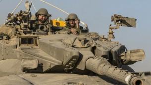 جنود اسرائيليون في  دبابة متمركزة على طول الحدود الإسرائيلية الجنوبية مع قطاع غزة في أعقاب الغارات الجوية الاسرائيلية 10 تموز 2014. AFP PHOTO / JACK GUEZ