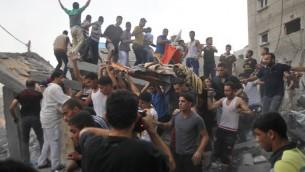 فلسطينيون يحملون جثة المقتولمن عائلة  غنام، بعد إزالتها من تحت أنقاض منزلهم بعد غارة جوية اسرائيلية على رفح في جنوب قطاع غزة، في 11 تموز 2014 AFP PHOTO / SAID KHATIB