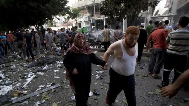 فلسطينيون يتفقدون موقع غارة جوية اسرائيلية في مدينة غزة  11 يوليو 2014. AFP PHOTO / MOHAMMED ABED
