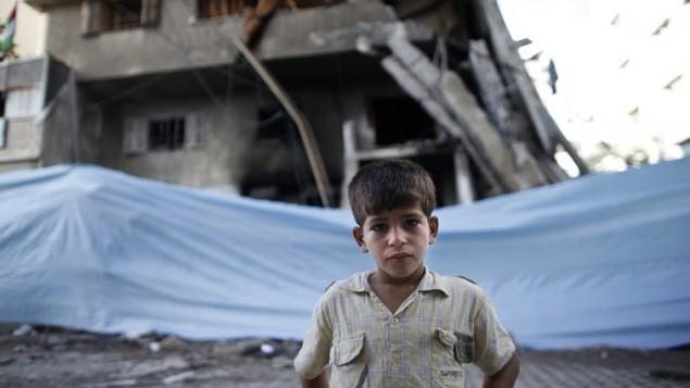 طفل فلسطيني يقف أمام القماش المشمع الملفوف حول مبنى دمر في أعقاب ضربة جوية اسرائيلية  14 يوليو  2014 في مدينة غزة.  AFP PHOTO / THOMAS COEX