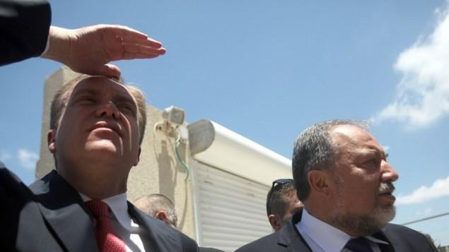 وزير الخارجية الإسرائيلي أفيغدور ليبرمان (R) وزير الخارجية النرويجي بورج بريند (L)  16 يوليو 2014، في زيارة الى منزل تضرر من صاروخ أطلقه نشطاء من قطاع غزة ضرب مدينة عسقلان. AFP PHOTO / DAVID BUIMOVITCH