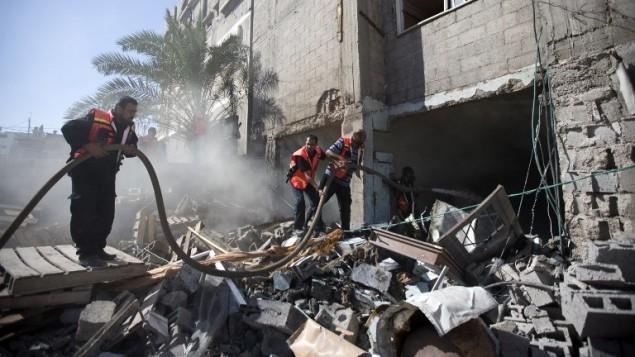 رجال الاطفاء الفلسطينيون في محاولة لاطفاء حريق شب في منزل دمر خلال غارة إسرائيلية، 16 يوليو  2014، في مدينة غزة. AFP PHOTO / MAHMUD HAMS