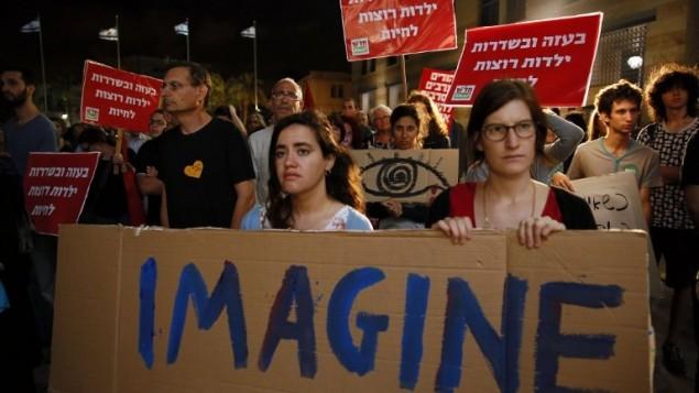 """نشطاء يساريون إسرائيليون من مجموعة """"مقاتلون من اجل السلام"""" يتظاهرون احتجاجا على العملية العسكرية الإسرائيلية في قطاع غزة يوم 17 يوليو 2014، في القدس. AFP PHOTO/GALI TIBBON"""