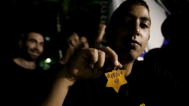 """ناشط يميني متطرف إسرائيلي يحمل ما  نجمة داود الصفراء مع الكلمة العبرية """"يهودي"""" لدعم العملية العسكرية الإسرائيلية في قطاع غزة  17 يوليو 2014، AFP PHOTO"""