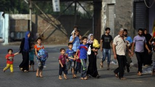 فلسطينيون يتركون بيوتهم في حي الشجاعية بعد القصف الإسرائيلي الثقيل 20 يوليو 2014 AFP PHOTO / MOHAMMED ABED