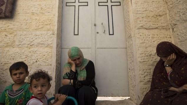 النساء والأطفال الفلسطينيين المشردين يجدون مأوى في كنيسة الروم الأرثوذكس  في مدينة غزة 23 يوليو 2014 . AFP PHOTO / MAHMUD HAMS
