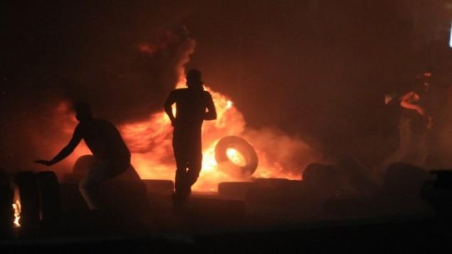 رجل فلسطيني يركض امام اطارات محروقة  حيث لا يقل عن 10،000 المتظاهرين الفلسطينيين احتشدو في مسيرة ضد الهجوم العسكري الاسرائيلي غلى قطاع غزة عند حاجز قلنديا الإسرائيلي، بين القدس ورام الله،  25 يوليو 2014AFP PHOTO/ABBAS MOMANI