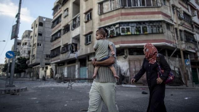 عائلة فلسطينية تمشي بين الانقاض من مبنى في وسط مدينة غزة  25 يوليو 2014.  AFP PHOTO / MARCO LONGARI