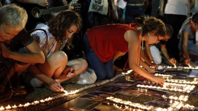 نشطاء يسار اسرائيلي يتظاهرون ضد الحرب في غزة  في ساحة رابين في تل أبيب  26 يوليو 2014، يضون الشموع ويطالبون بنهاية الهجوم العسكري الإسرائيلي على قطاع غزة. AFP PHOTO / THOMAS COEX