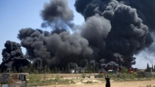 رجل فلسطيني، يقف امام اللهيب الصاعد من مصنع الكهرباء الوخيد الذي يوصل كهرباء لاهل غزة، بعد غارة اسرائيلية 29 يوليو 2014 (مخمود حمص/ أ ف ب)