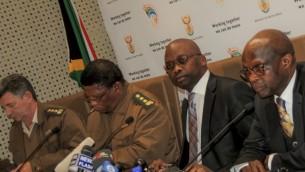 """وزير العدل في جنوب أفريقيا مايكل موستاذا (الثاني عن اليمين) يحضر مؤتمر صحفي عقد في 10 يوليو 2014 حول عقيد شرطة عهد الفصل العنصري يوجين دي كوك المعروف باسم """"رئيس الشر"""" AFP PHOTO / STEFAN HEUNIS"""